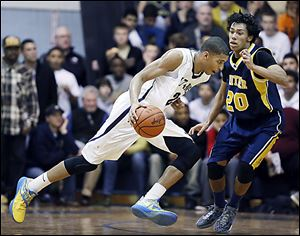 Marc Loving of St. John's drives past Whitmer's Chris Boykin. Loving has signed to play at Ohio State.
