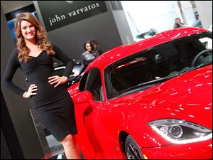 A model poses with a Dodge Viper.