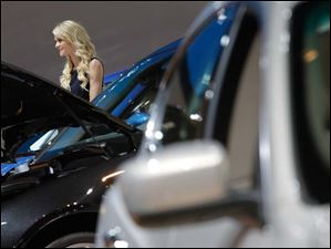 A model poses with Maserati cars at the North American International Auto Show.