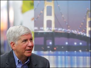 Michigan governor Rick Snyder speaks with the media at the North American International Auto Show in Detroit.