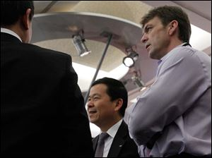 Jeep CEO Mike Manley, right, speaks with Wang Xia, left, chairman, China Council for the Promotion of International Trade, Automotive Sub-Council, and Qing Hong Zeng, center, president of the  Guangzhou Automobile Group, during a press conference at the North American International Auto Show.