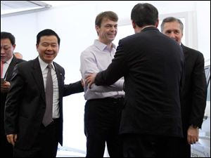 Wang Xia, left, president of the Guangzhou Automobile Group,  Jeep CEO Mike Manley, center, and Fiat S.p.A. Chief Operating Officer of the Europe, Africa and Middle East Regional Operations Group, Alfredo Altavilla, right, speak with a GAC official.