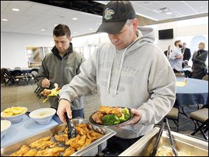 Walleye coach Nick Vitucci, right,  tucks into a tray of fried Walleye while player Pat Knowlton, left, gets some salad.