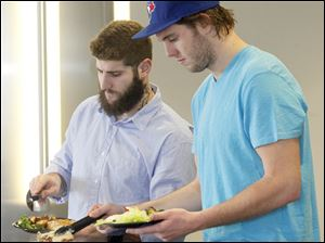 Walleye players Cody Lampl, left, and Ben Woodley, right, tuck into a tray of fried Walleye.