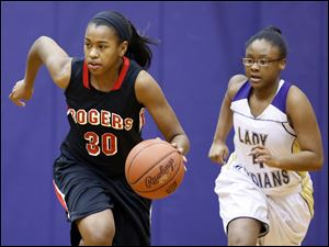 Rogers' Akienreh Johnson moves the ball down court as Waite's Kayla May trails her.