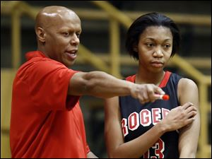 Rogers head coach Lamar Smith gives instructions to Toriana Easley.
