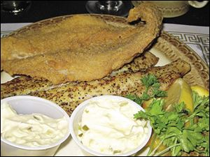 Two pieces of Lake Superior whitefish, one baked with lemon and seasoning, the other deep fried.