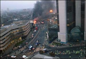 In this overhead view showing smoke and flames at the site of a helicopter crash in central London, as people gather to view the scene shortly after the incident.