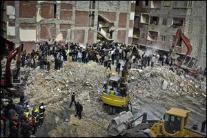 Egyptians stand in rubble after an eight story building collapsed in Alexandria, Egypt.