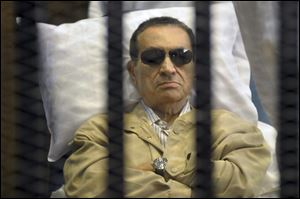 Egypt's ex-President Hosni Mubarak lays on a gurney inside a barred cage in the police academy courthouse in Cairo, Egypt, last July.