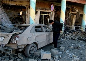 A man inspects his destroyed car at the scene of a bomb attack in Kirkuk, 180 miles north of Baghdad, Iraq