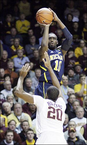 Michigan guard Tim Hardaway, Jr., shoots over Minnesota guard Austin Hollins. Hardaway scored 21 points.