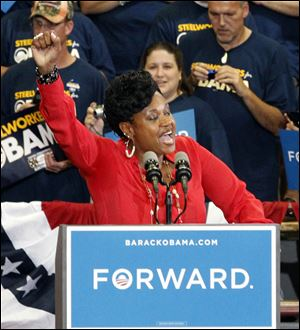 A Toledo autoworker, Kenyetta Jones, introduces President Barack Obama to a crowd gathered at  Scott High School on Sept. 3, 2012.