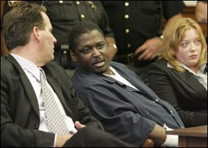The scheduled 2014 execution of convicted murderer Wayne Powell, shown here flanked by his attorneys during his Lucas County Common Pleas Court trial in 2007, has been canceled.
