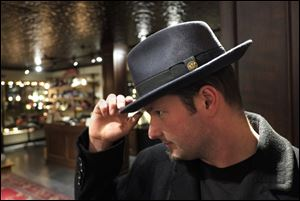 Adam Caine tries on a hat at Goorin Bros. in Uptown, Minneapolis.