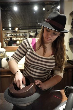 Libby Ryan, of Goorin Bros. in Uptown, Minneapolis, stretches out a hat. The new old-school men's hat shop has opened in Uptown, just as the trend has hit its stride.