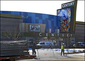 Workers with American Fence remove the fence from around the Century theater in Aurora, Colo. on Thursday.