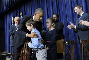 President Barack Obama, accompanied by Vice President Joe Biden hugs eight-year-old letter writer Grant Fritz during a news conference on proposals to reduce gun violence Wednesday in Washington.