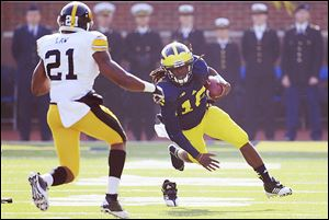 Michigan quarterback Denard Robinson loses his shoe as he runs for a first down last fall against Iowa.