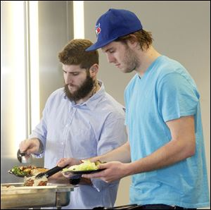Hockey players Cody Lampl, left, and Ben Woodley, right, help themselves to fried walleye at a luncheon held at the Huntington Center. Some players had never sampled the Lake Erie specialty.