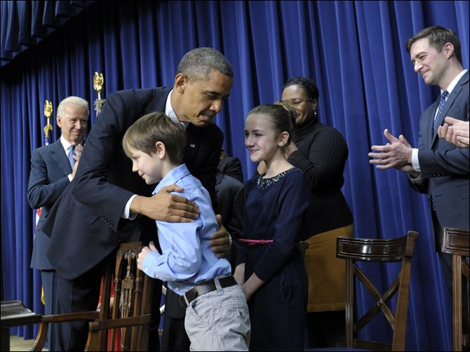 APTOPIX Obama Gun Control plan President Barack Obama, accompanied by Vice President Joe Biden hugs eight-year-old letter writer Grant Fritz during a news conference on proposals to reduce gun violence Wednesday in Washington.