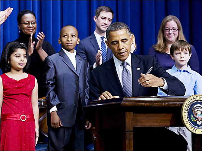 President Barack Obama, accompanied by children who wrote to him about gun violence, signs executive orders aimed at reducing violence.