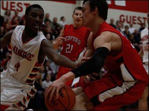Bedford's Jackson Lamb battles Monroe players as he goes in for a layup.