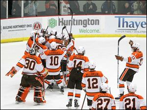 Bowling Green State University players mob goalie Andrew Hammond (1) after the Falcons defeat Western Michigan University 3-2.