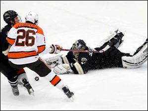 BGSU's Mark Cooper (26) is held up by a Western Michigan player as Bronco goalie Frank Slubowski (1) makes a diving save during the first period.