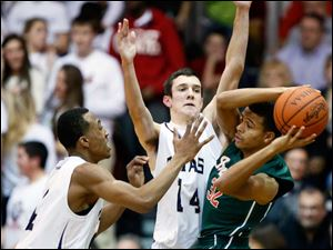 St. John's Jesuit's  Anthony Glover (4) and Chris Stearns (14) defend against Central Catholic's Marcus Winters (32).