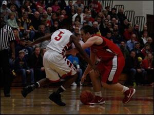 Bedford's Brad Boss (5) dribbles low trying to sneak past Juwan Johnson (5) of Monroe.