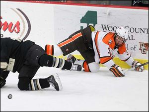 BGSU's Connor Kucera (3) and WMU's Josh Pitt (10) collide going for the puck during the first period.