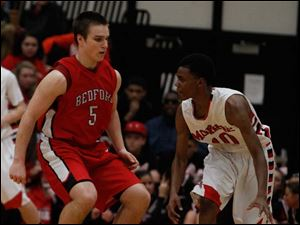 Monroe's Raynard Pouncy (10), dribbles around Bedford's Brad Boss (5).