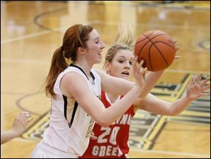 Perrysburg's Sarah Baer (23) looks to pass while being  guarded by Bowling Green's Livvy Dill (20).