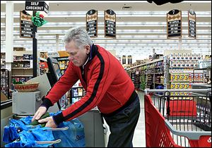 Darrel St. Aubin bags his groceries after shopping in Kirkwood, Missouri. Stores are targeting male shoppers with more man-centric displays and gender-neutral packaging.