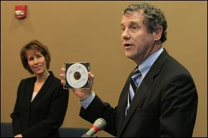 Sen. Sherrod Brown (D-Oh.), right, with a copy of the foreclosure training manual ABLE created for attorneys to use to help clients. At left, rear, is Luckey Mayor Belinda Brooks.