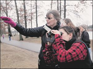 Diane DeYonker, of Whitehouse, left and rear, points to the location of a Downy Woodpecker to Kate Zimmerman, of Oak Harbor.