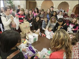 Students sort items that have been collected for the homeless. The collection is part of an outreach program coordinated by Lourdes University students under the direction of Sr. Janet Doyle.