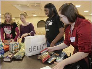 Sorting out donated food are, from left: Alexa Carr, 14, a ninth grader at Central Catholic; December  Anderson, 14, a ninth grader at Central Catholic; Noma Aguebor, 15, a sophomore at Sylvania Southview; and Breanne Briskey, 17, a junior at Swanton.
