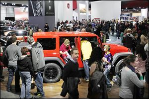 People crawl in and out of a Jeep Wrangler Unlimited Moab edition during opening day of the North American International Auto Show in Detroit. Jeep also had several Wranglers on the show floor.