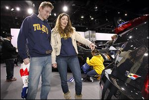 Josh Pettrey of  Ypsilanti, Mich., and Sarah Przybylski of Peters-burg, Mich., look at the back of a Cadillac CTS on the first day of the North American International Auto Show in Detroit.