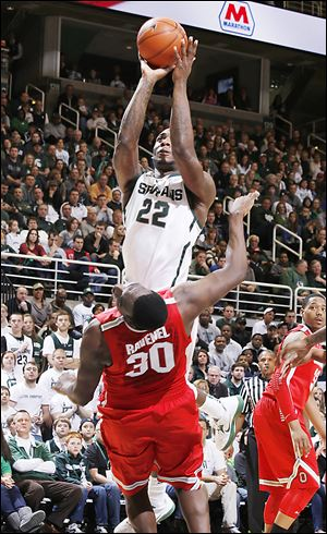 Michigan State's Branden Dawson (22) goes over Ohio State's Evan Ravenel (30) for a shot during Saturday's game in East Lansing, Mich. The Buckeyes fell to 13-4 overall, 3-2 in the Big Ten.