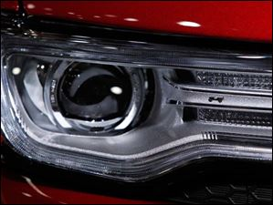 A Jeep Grand Cherokee headlight sports a silhouette of a Jeep.