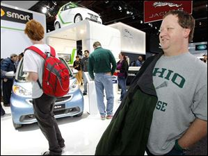 Trevor Heim, 18, of Maumee, left, and his father Scott Heim check out the Smart car exhibit.