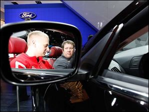 Brian Schwartz of Huron, left, and Kevin O'Brien, a BGSU student from Marion, Ohio, are seen in the review mirror as they check out an Infiniti IPL G.