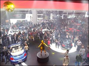 A dancer helps draw in the crowd to the Volkswagen display.