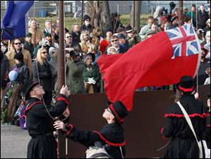 Flag bearers raise the British flag during the 200th anniversary of the Battles of the River Raisin at the River Raisin Battlefield Park.