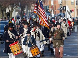 Many reenactment units gather and march down East Front Street to the River Raisin National Battlefield Park Visitor Center during the 200th anniversary of the Battles of the River Raisin in Monroe, Mich.