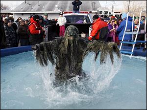 Jason Vacek, dressed in a Ghillie suit, emerges from the pool.