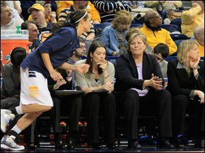 Toledo head coach Tricia Cullop, seated second from left, calls her in to sub for Inma Zanoguera, after Zanoguera picked up her fourth foul with just over three minutes to play in the second half. Seated at left is assistant coach Katie Griggs, and associate head coach Vicki Hall, right.